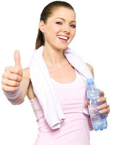 Sportliche Frau mit Wasserflasche macht Topdaumen